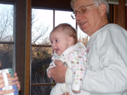 Clara smiling at Mom and in Grandpa's arms